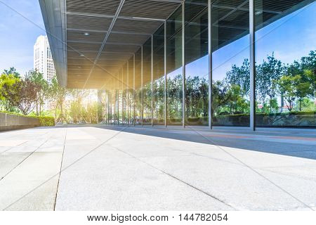 trees and blue sky reflected on clean glass wall,china.