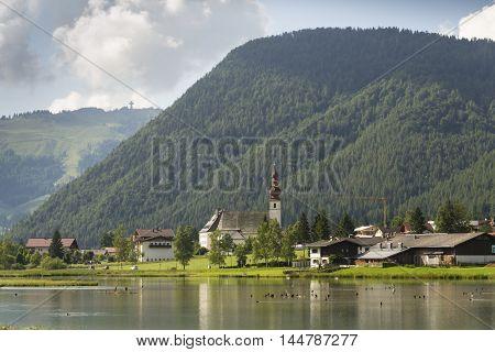 Sankt Ulrich am Pillersee with Jakobskreuz on the Buchensteinwand summit poster