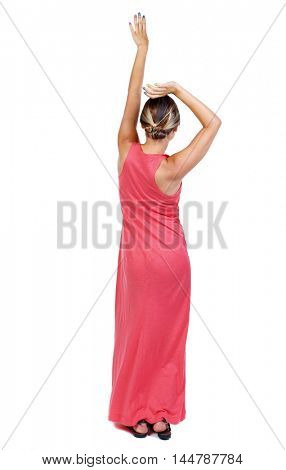 back view of dancing young beautiful woman. girl watching. A slender woman in a long red dancing waving his arms above his head.