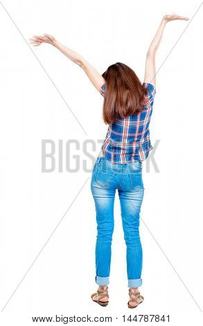 Back view of beautiful woman welcomes. Girl in plaid shirt with short sleeves is raising his arms above his head.