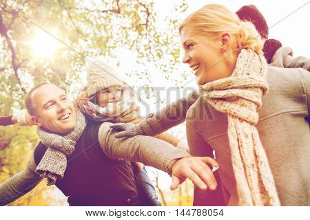 family, childhood, season and people concept - happy family having fun in autumn park