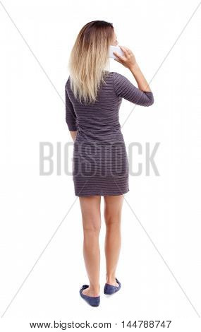 back view of a woman talking on the phone. backside view of person. Blonde in violet short dress talking on the phone and looking up.