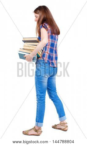 Girl carries a heavy pile of books. back view. Girl in plaid shirt trying to hold books in their hands.