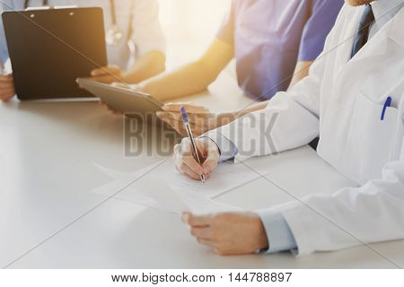education, profession, people and medicine concept - close up of happy doctors with tablet pc computer and papers at seminar or hospital