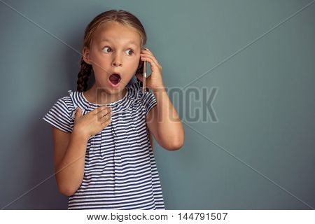 Cute little girl in dress is talking on the mobile phone showing surprise and smiling standing on gray background