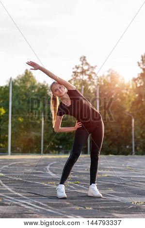 Young attractive blonde woman doing warming up exercises, fitness workout outdoors.