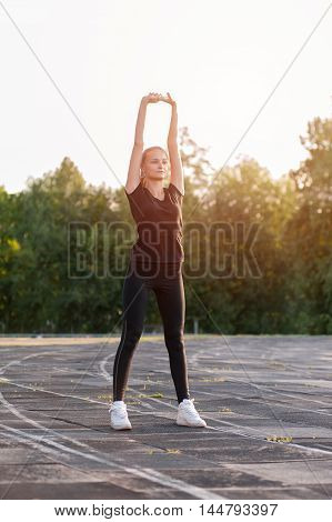 Young cute girl warming up before fitness workout outdoors