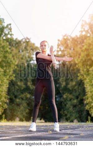 Young blonde woman stretching before workout outdoors