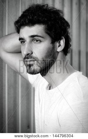 Black-and-white portrait of a calm handsome young man leaning to the wall outdoor.