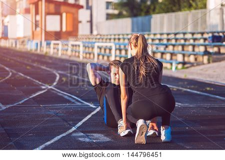 Young attractive adults training outdoors, doing sit ups exercises.
