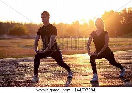 Two silhouettes of young sporty man and woman warming up outdoors at sunset. Fitness or running workout outdoors