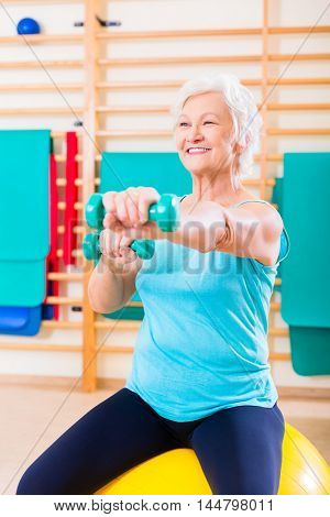 Senior woman doing fitness sport in gym with dumbbells