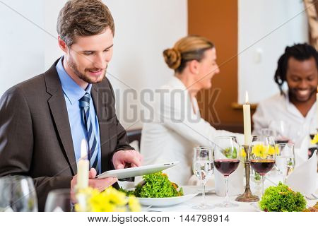 Man in restaurant at business lunch with his team checking emails on tablet computer, food and drink on the table in background