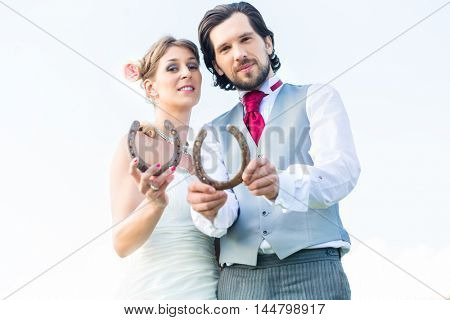 Wedding bride and groom showing horseshoe symbol for luck