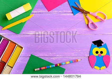 Paper owl crafts, modeling clay set, color paper sheets, scissors, glue stick, pencil on wooden background with blank space for text. Back to school background for kids, students. School supplies