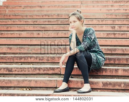 Sad lonely young woman sitting on steps. Portrait of serious girl with facial expression outdoors.