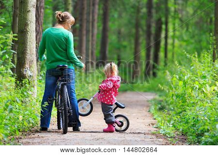 mother and little daughter riding bikes in summer forest, family sport