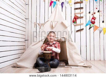 boy sitting on the floor and playing drum near wigwam in decorated wooden room