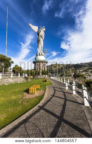 QUITO ECUADOR - JUNE 14 2015: The monument of the Madona of Panecillo looks magnificent in the morning on top of the small hill in the center of the city of Quito.