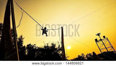 happy little girl flying on swing in sunset background