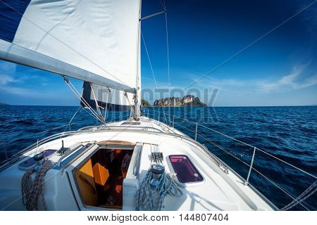 Sailing vessel moving under sails in the calm sea