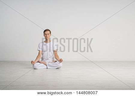 Young man meditating in Lotus position on the floor