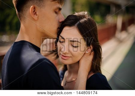 Young happy couple in love in a romantic moment of man kissing his woman in a forehead