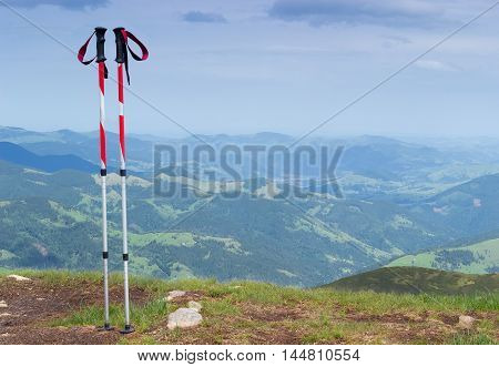 Pair of trekking poles made from three aluminum sections on a background of mountain ridges and valleys