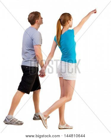 Back view of walking young couple (man and woman) pointing. going tourists in shorts considering attractions. Rear view people collection. backside view of person. Isolated over white background
