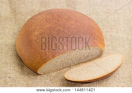 Partly sliced brown wheat and rye hearth bread on a sackcloth