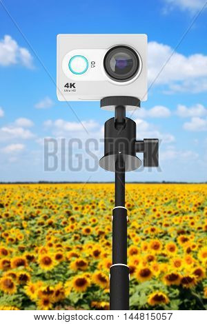 Small Ultra HD Action Camera with Extensible Selfie Stick Monopod in front of landscape background. 3d Rendering