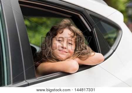 Cheerful little girl enjoying car ride. Cute little girl during a summer road tip. Beautiful little girl looking out the car window. Summer vacation concept.
