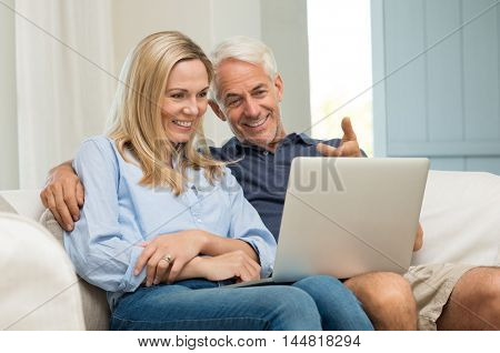 Mature man and his wife working with laptop at home. Senior couple using ecommerce in internet with computer. Cheerful senior couple sitting on sofa at home and using laptop.