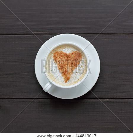 frothy coffee with cinnamon sprinkled in heart shape on a dark wooden background top view / coffee and cinnamon anyway love