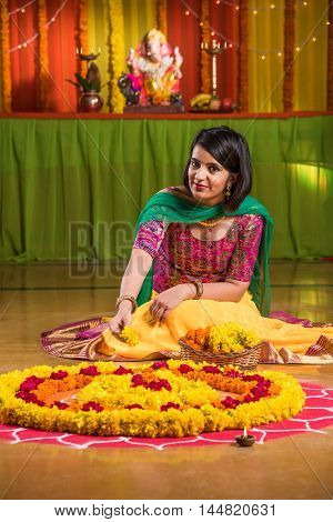 Indian girl making rangoli using flower, asian girl making flower rangoli on floor on ganesh festival day