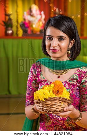 Indian smart girl holding flower basket on ganpati festival