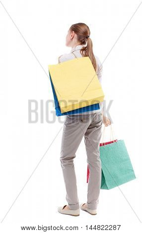 back view of woman with shopping bags. backside view of person. Isolated over white background. Skinny girl in white denim suit is throwing shopping bags on her back.