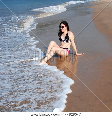 Happy beautiful girl in a bikini is sitting on the beach at the water's edge