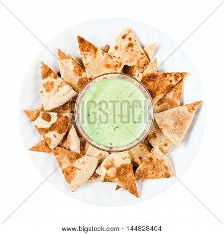 Delicious homemade nachos with green guacamole on a round white plate. Traditional Mexican food. Top view isolated on white background