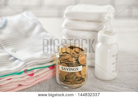 Parenting expenses concept. Glass can with coins, feeding bottle and pile of diapers