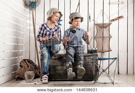 two little children sitting on big old chest prepare bait on rod for fishing