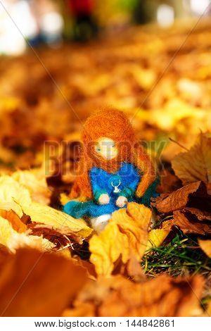 Beautiful felting elf in the autumn leaves