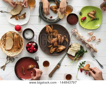 family having dinner with roasted chicken wings top view