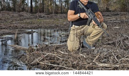 Man kneeling next to some water with an AR-15 and handgun