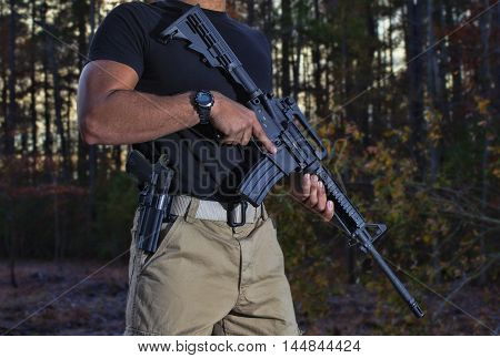 Man with a sidearm and Ar-15 that is on guard in the woods