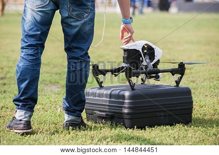 Man presses a button to launch drone with camera at stadium