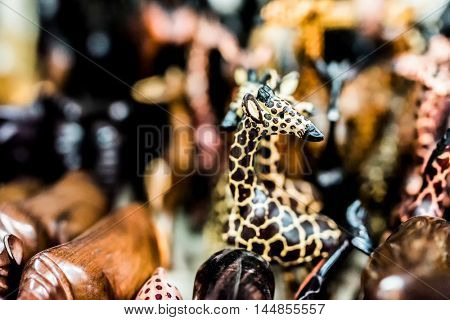 woodcarved giraffe and other animal toys at african flea market stall