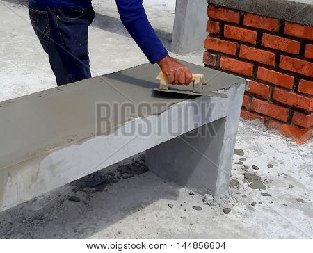 workman using hand trowel to smooth wet concrete over a new park bench  , Songkhla, Thailand