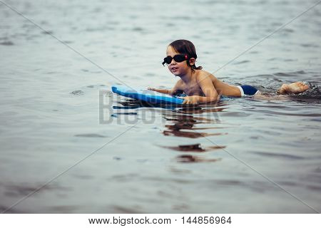 Portrait of cute boy in goggles floating on board in sea