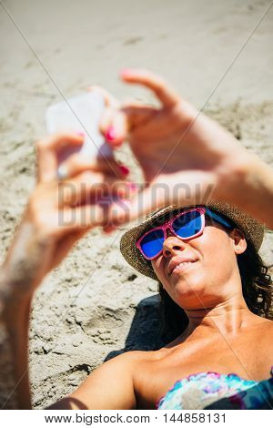 Portrait of smiling adult woman in hat and sunglasses taking self-portrait via cell phone